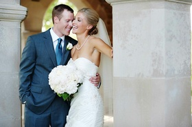 Groom in navy suit with bride in strapless white dress