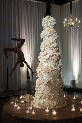 Seven layer cake with sugar flowers acrobat in background aerial dancer candle votives
