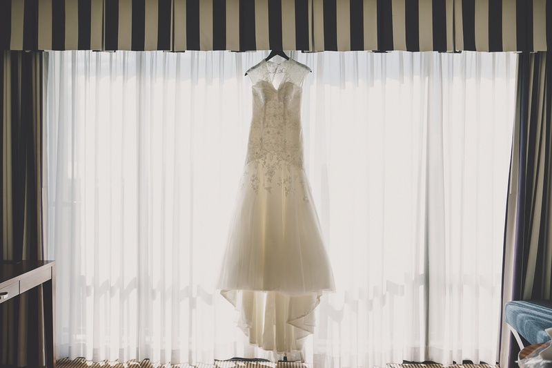 Embroidered bridal gown hanging on window drapes