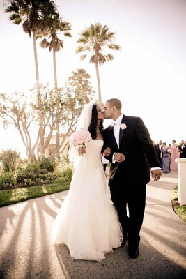 African American bride and groom kiss under palm trees