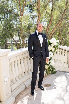 Groom on staircase with white flowers tuxedo tom ford bow tie white pocket square