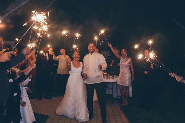 Bride and groom hold sparklers at wedding reception