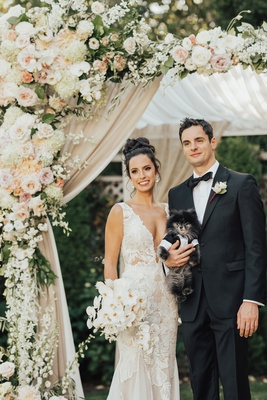 bride and groom under chuppah with little pomeranian pup dog puppy in tuxedo outfit
