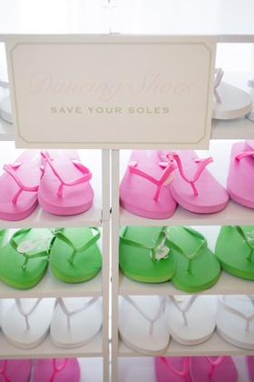 Pink, green, and white flip flops in white cubby