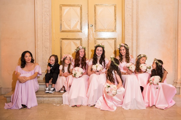 One ring bearer and flower girls junior bridesmaids in pink dresses with bouquets and flower crowns
