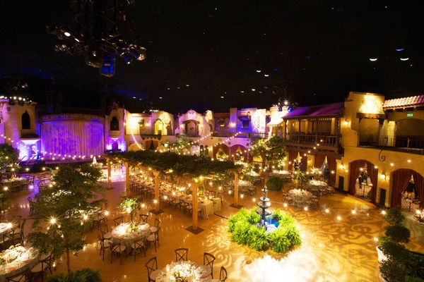 Wedding reception that looks like outdoor venue ballroom high ceilings balcony fountain trees lights