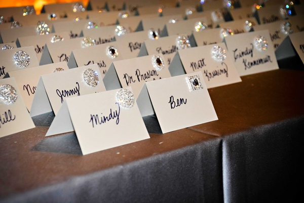 Silver buttons on white tent place cards with hand written names in cursive