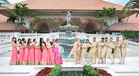 indian-american wedding party in traditional attire pretend to pull bride and groom apart