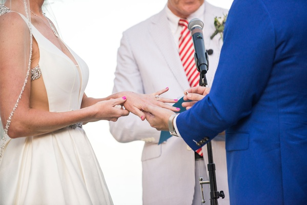 groom places ring on bride's finger at beach wedding