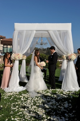Bride and groom at oceanfront ceremony under chandelier