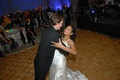 Bride in a Reem Acra gown dances with groom in a black tuxedo