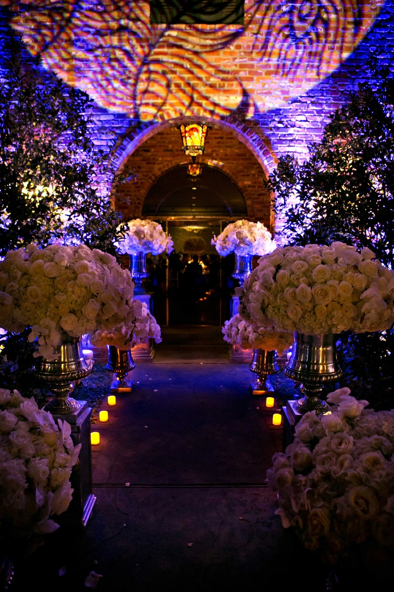 wedding reception places in twin cities%0A     Purple lighting outside wedding venue with lush white rose flower  arrangements leading to room