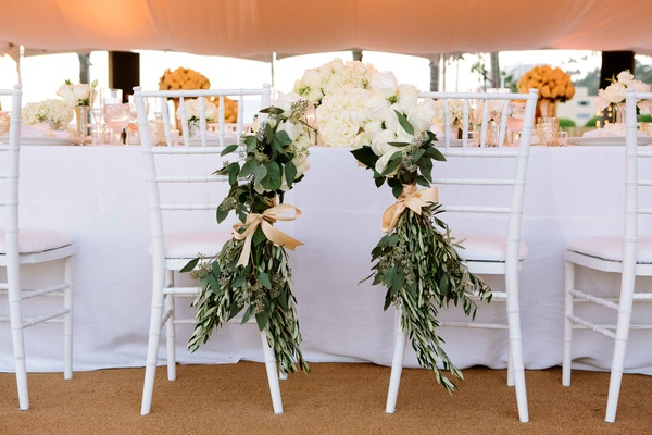Beach tented wedding reception with newlywed's chairs joined by greenery, white roses, hydrangeas