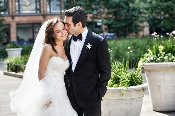 Bride in wedding dress gets kissed by groom on cheek