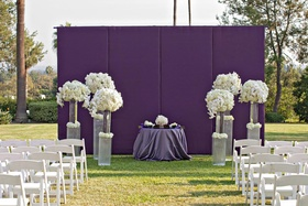 White chairs and violet wall with floral arrangements