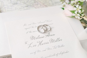 wedding invitation grey calligraphy script with bride's rings eternity band and solitaire engagement