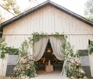 White wash wood barn with drapery greenery wood boards with escort cards for reception