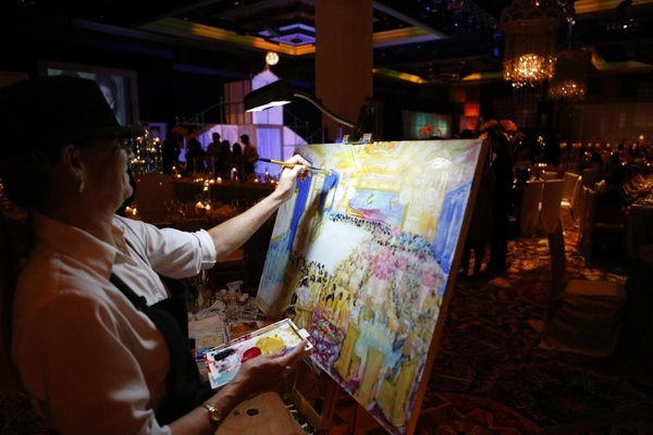 Wedding reception with a painter painting a the celebration as it was taking place