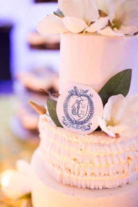 Wedding cake with blue monogram and magnolia flower leaves cake topper ruffles
