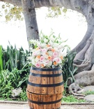 barrels displaying akimo roses, pink roses, peach roses, dusty miller