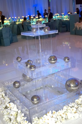 glass fountain with silver balls and white flowers