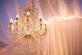 Gold crystal chandelier illuminates wedding drapery