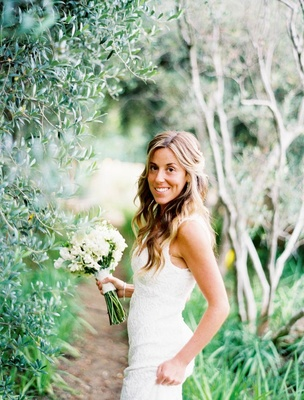 Bride in a Monique Lhuillier lace gown with a bouquet of white flowers