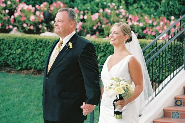 Bride holds father of the bride's hand at wedding ceremony