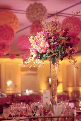 Wedding reception table with a centerpiece of pink, orange and yellow flowers