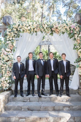 groom in tuxedo with groomsmen in taupe bow ties boutonnieres ceremony arch stone steps