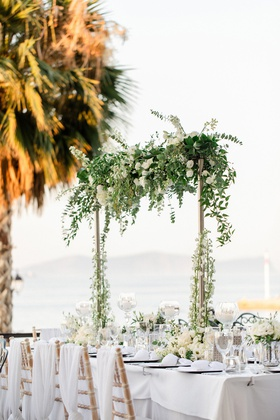 wedding head table floral installation with greenery, white hydrangeas, and roses