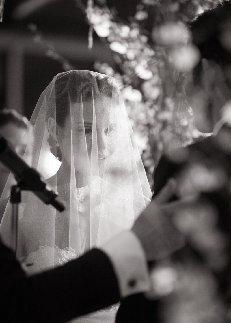 black and white picture of a bride with her blusher over her face during the ceremony