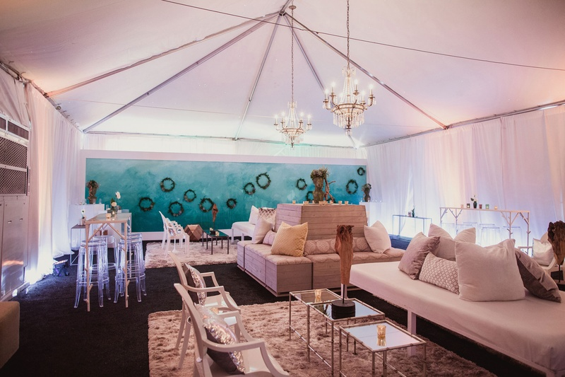 tented reception area with lounge seats, succulent wreaths