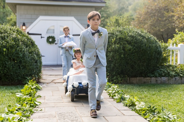 two ring bearers pulling two flower girls in blue wagon down aisle outdoor wedding