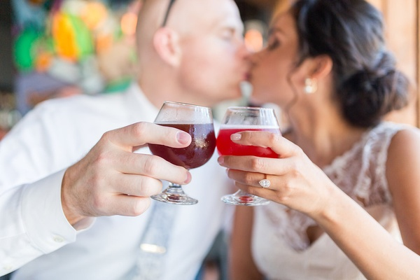 Bride and groom kiss at restaurant with craft cocktails red libations engagement ring pear shape