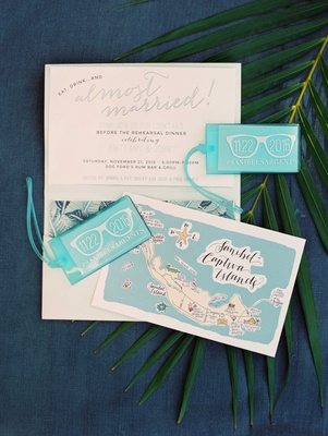 Map of destination wedding location with rehearsal dinner invitation palm trees suitcase name tags