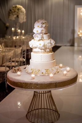 Wedding cake white and gold layers orchid flowers on top tiers candles on table