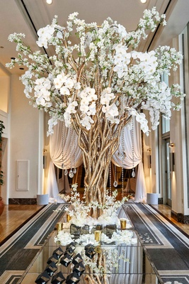 Escort card table with gold branches, crystals, white orchids and flowers, black escort cards roses