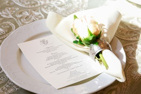 Wedding reception place setting menu card on top of white plate with napkin and single pink rose