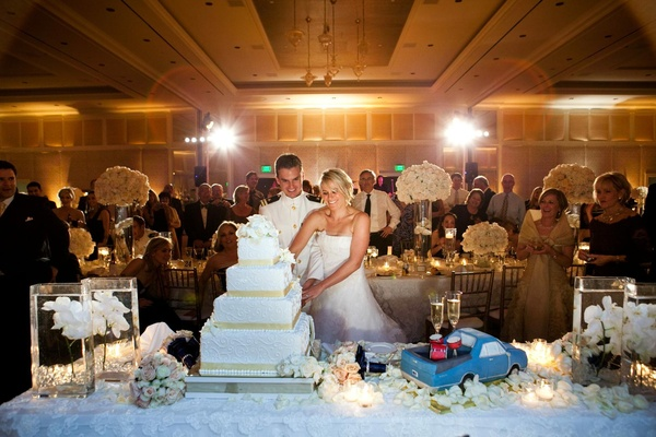 Bride and groom cut wedding cake next to groom's cake