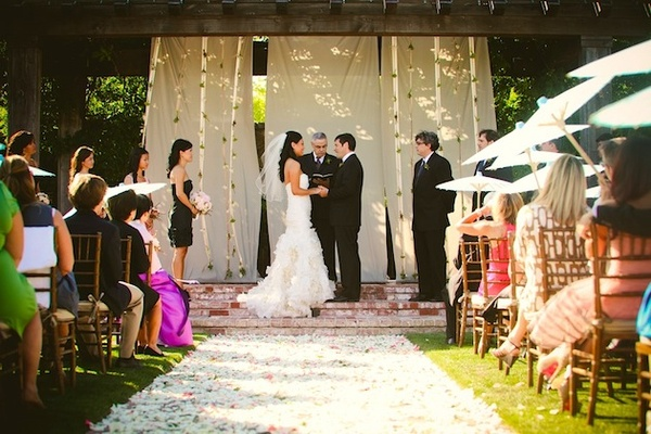 Petal-covered aisle and wooden wedding canopy