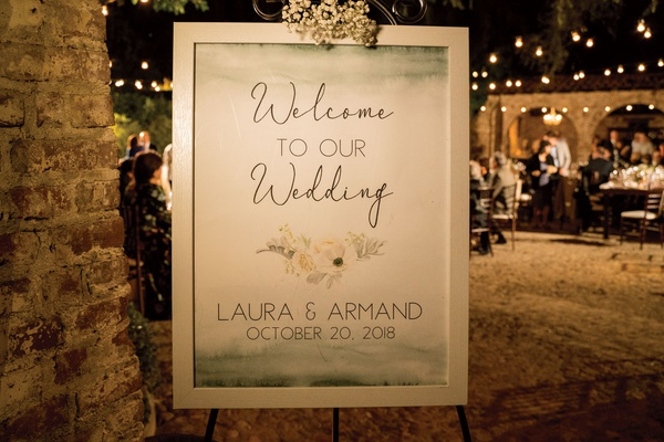 wedding welcome sign with watercolor at the top and bottom and floral details