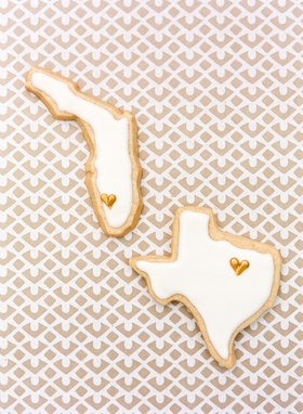 Frosted cookies in the shape of Florida and Texas served at a wedding