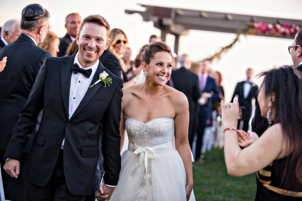 Bride in Monique Lhuillier dress and groom hold hands walking up aisle at outdoor ceremony