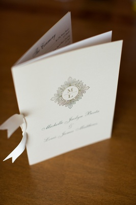 White bow tied to wedding program with monogram