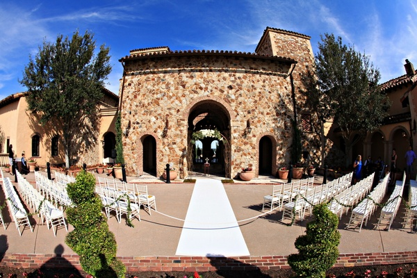 White chairs and aisle runner leading to stone archway