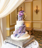 wedding cake four layer with purple blue grey brush stroke design and flowers on top silver base