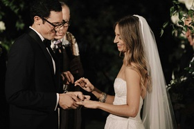 bride at wedding ceremony veil long hair groom putting on ring with glasses