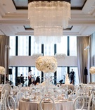 wedding reception ballroom view of chicago chandelier white flower arrangements light grey linen