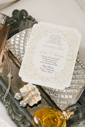 Formal wedding invitation with black script couple's names in gold calligraphy and gold scroll